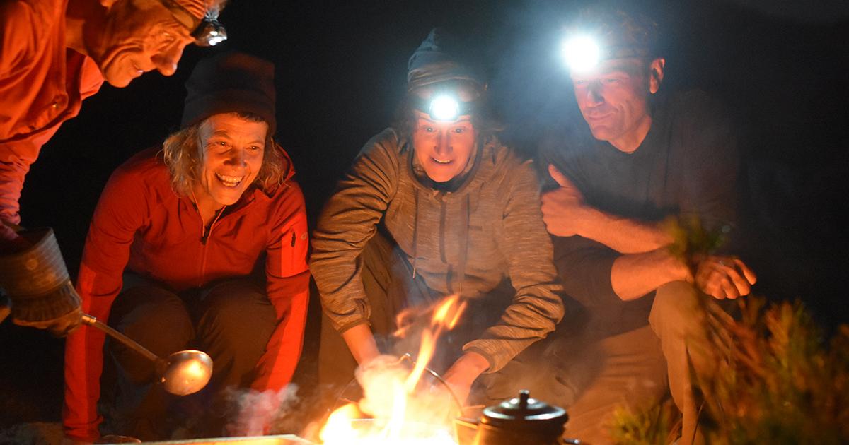 4 Menschen die in der Nacht, teilweise mit Stirnlampen strahlend auf eine Kochstelle am Feuer blicken.